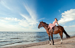 Beautiful girl with horse on seacoast Stock Images