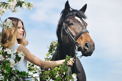 Beautiful girl and horse in spring garden Stock Image