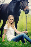 Beautiful girl and horse in spring garden Stock Photography