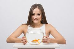 Beautiful girl hugged an aquarium with goldfish Stock Image
