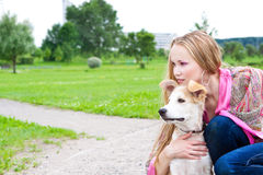 Beautiful girl hugging his dog. Beautiful girl looks into the distance, hugging his dog Stock Image