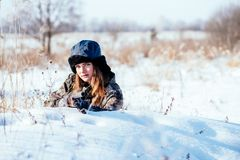 A beautiful girl hunter in camouflage suit with binoculars and a royalty free stock photos