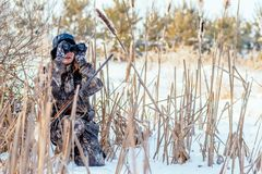 Beautiful girl hunter in camouflage suit with binoculars and a g royalty free stock images