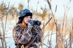 Beautiful girl hunter in camouflage suit with binoculars and a g stock photos