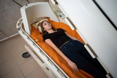 Beautiful girl in a hyperbaric chamber, oxygen treatment. Medical chamber stock photography