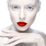 Beautiful girl in the image of albino with red lips and white eyes. Art beauty face. Picture taken in the studio on a white background Royalty Free Stock Image