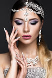 Beautiful girl in image of Arab bride with expensive jewelry, oriental make-up and bridal manicure. beauty face. Royalty Free Stock Image