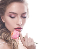 Beautiful girl in image of bride with flower. Model with nude makeup and a rose in her hand. Stock Photo