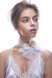 Beautiful girl in image of bride with flower orchid on her neck. Model with nude makeup and silk underwear. Royalty Free Stock Photo