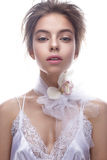Beautiful girl in image of bride with flower orchid on her neck. Model with nude makeup and silk underwear. Stock Photography