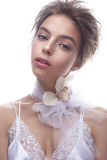 Beautiful girl in image of bride with flower orchid on her neck. Model with nude makeup and silk underwear. Royalty Free Stock Image