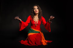 Beautiful girl in the image of a gypsy on a dark background. Professional acting. Beautiful costume and professional makeup. Photos for magazines, posters and royalty free stock images