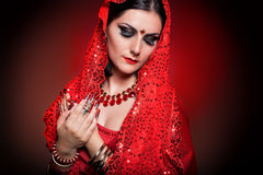 Beautiful girl in the image of Indian woman in a red sari with beautiful patch acrylic nails in oriental style in the studio Stock Images