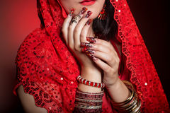 Beautiful girl in the image of Indian woman in a red sari with beautiful patch acrylic nails in oriental style in the studio Stock Image