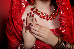 Beautiful girl in the image of Indian woman in a red sari with beautiful patch acrylic nails in oriental style in the studio Stock Photography