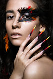 Beautiful girl in image of Phoenix bird with creative makeup and long nails. Manicure design. beauty face. Stock Image