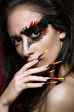Beautiful girl in image of Phoenix bird with creative makeup and long nails. Manicure design. beauty face. Royalty Free Stock Image