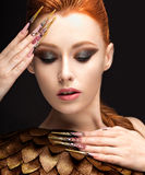 Beautiful girl in the image of the Phoenix with bright makeup, long fingernails and red hair. Beauty face. Picture taken in the studio on a black background Stock Images