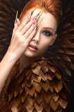 Beautiful girl in the image of the Phoenix with bright makeup, long fingernails and red hair. Beauty face. Royalty Free Stock Photo