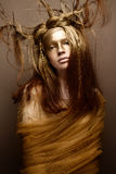 Beautiful girl in the image of a tree with branches in her hair. The model with creative make-up. The photo was taken in a studio. Beautiful face Stock Images
