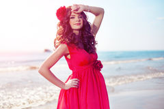 Beautiful Girl In A Bright Red Dress By The Sea. Against The Background Of The Summer Lanshaft. Young Romantic Woman In Royalty Free Stock Photography