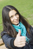Beautiful Girl In A Park Smiling. Thumb Sign OK Royalty Free Stock Image