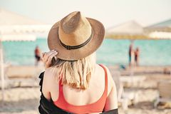 Free Beautiful Girl In A Red Bikini And Straw Hat On The Beach. Back View. White Sand, Blue Water And Beach Umbrellas On The Stock Photography - 159169552