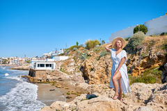 Free Beautiful Girl In A Summer Dress And Hat On The Seashore Near A Background Old City Europe. Mediterranean Sea, Sitges Royalty Free Stock Photos - 96603668