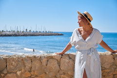 Free Beautiful Girl In A Summer Dress And Hat On The Seashore Near A Background Old City Europe. Mediterranean Sea, Sitges Stock Photography - 96604032