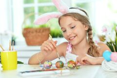 Beautiful Girl In Bunny Ears Painting Eggs For Easter Holiday Royalty Free Stock Images