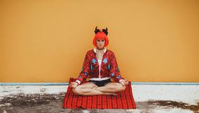 Beautiful Girl In Red Devil Costume Sitting In Yoga Pose In Anticipation Of Halloween. Wears A Red Wig And Horns. The