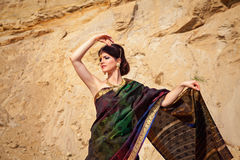 Beautiful girl with indian jewelry against sand background Stock Photo