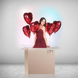 Beautiful girl inside a cardboard box with red ballooons Royalty Free Stock Image