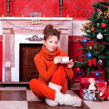 Beautiful girl inside a red vintage room with christmas decor Royalty Free Stock Photo