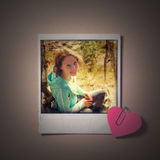 Beautiful girl instant photo and small red paper heart. Royalty Free Stock Image