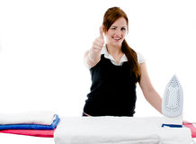 Beautiful girl irons colored towels Royalty Free Stock Image