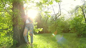 Beautiful girl in jeans clothes posing at sunset at the tree in the forest. stock video