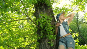 Beautiful girl in jeans clothes posing at sunset at the tree in the forest. stock video footage