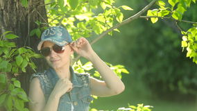 Beautiful girl in jeans clothes posing at sunset at the tree in the forest. stock footage
