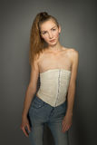 Beautiful girl in jeans and a cream corset Stock Photography