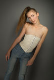 Beautiful girl in jeans and a cream corset Royalty Free Stock Image
