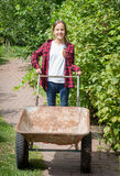 Beautiful girl in jeans and shirt with wheelbarrow at rustic gar Stock Photo