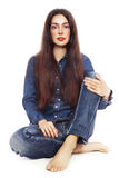Beautiful girl in jeans sitting over white background Stock Photo