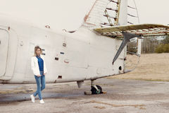 Beautiful girl in jeans and a white jacket standing near an old airplane on a cloudy day Royalty Free Stock Photos