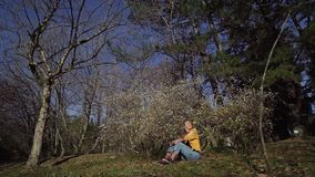 Beautiful girl in jeans and a yellow jacket is sitting on the green grass in the blooming garden. A beautiful girl in jeans and a yellow jacket is sitting on the stock video footage