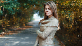 Beautiful girl in a jersey standing in park. Autumn in Europe Stock Image