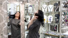 Beautiful girl in a jewelry store chooses jewelry. Jewelry on a white background , earrings, pendant, with green stones and crystals shimmering in the light stock video