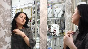Beautiful girl in a jewelry store chooses jewelry. Jewelry on a white background , earrings, pendant, with green stones and crystals shimmering in the light stock video footage