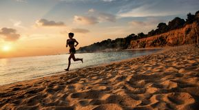 Beautiful girl is jogging on a beach. In Greece in Skiathos Island royalty free stock image