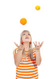 Beautiful girl juggling with fruit Stock Photography